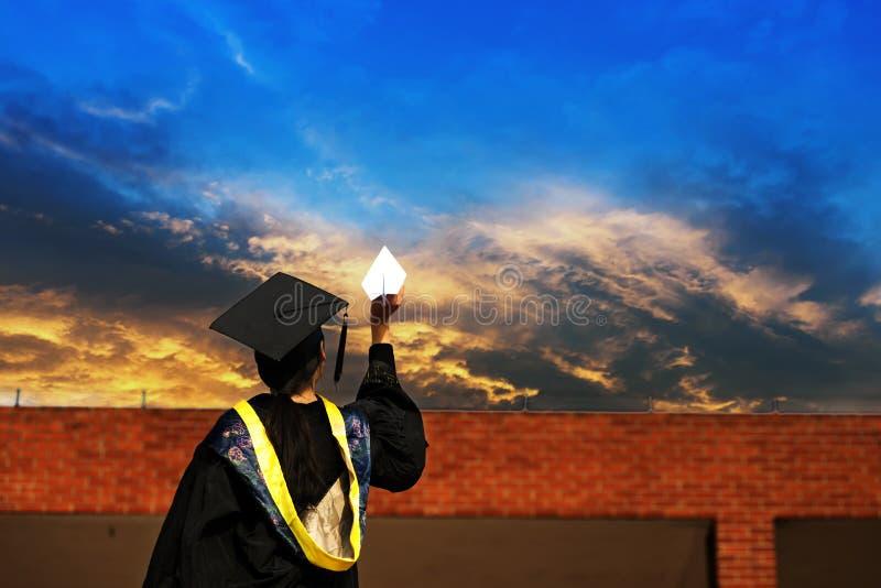 Vrouwelijke gediplomeerde dragende graduatietoga stock afbeelding
