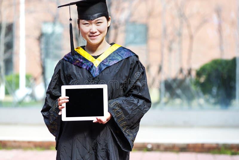 Vrouwelijke gediplomeerde dragende graduatietoga royalty-vrije stock foto