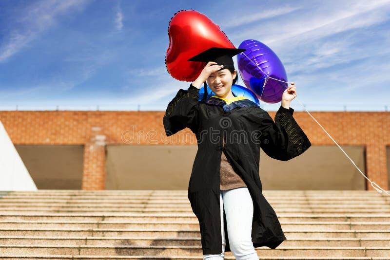 Vrouwelijke gediplomeerde dragende graduatietoga royalty-vrije stock afbeelding