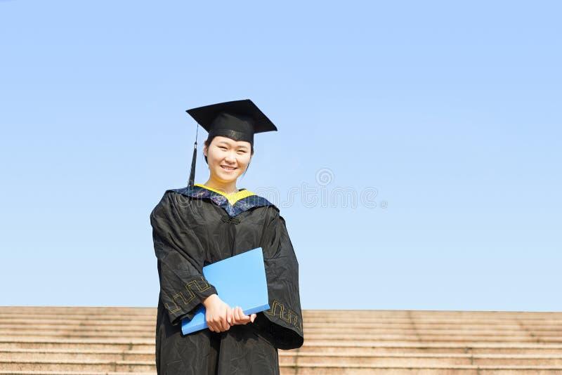 Vrouwelijke gediplomeerde dragende graduatietoga stock foto's