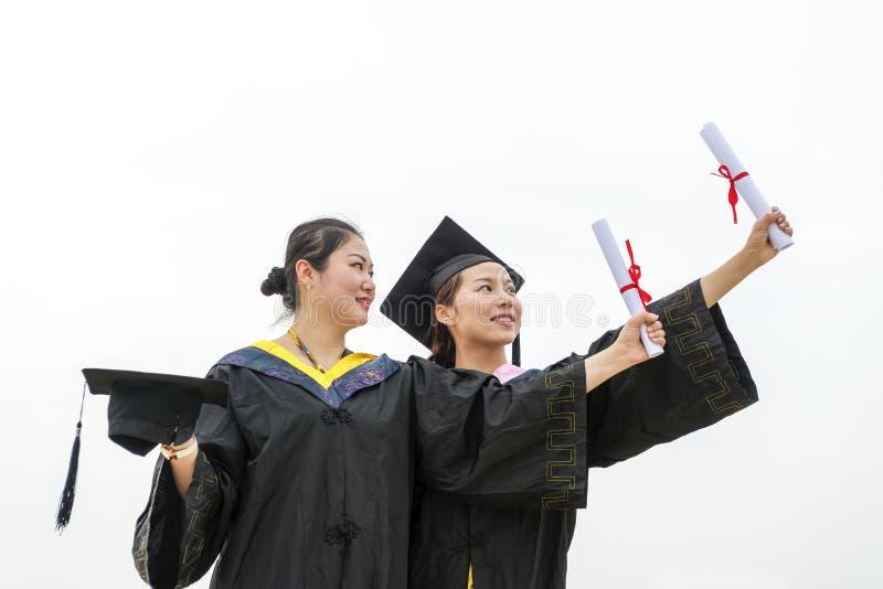 Vrouwelijke gediplomeerde dragende graduatietoga stock afbeeldingen