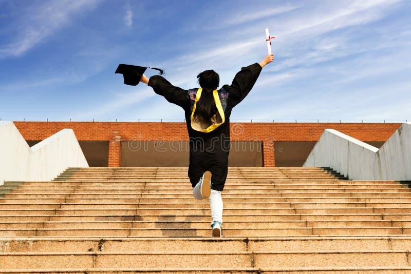 Vrouwelijke gediplomeerde dragende graduatietoga royalty-vrije stock foto's