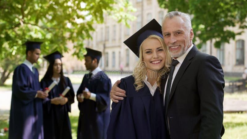 Vrouwelijke gediplomeerde koesterende papa en het glimlachen in camera, succesvolle toekomst, carrière stock afbeelding