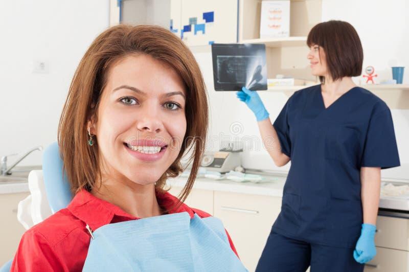 Vrouwelijke geduldige het glimlachen en vrouwentandarts arts die radiogr controleren royalty-vrije stock foto's