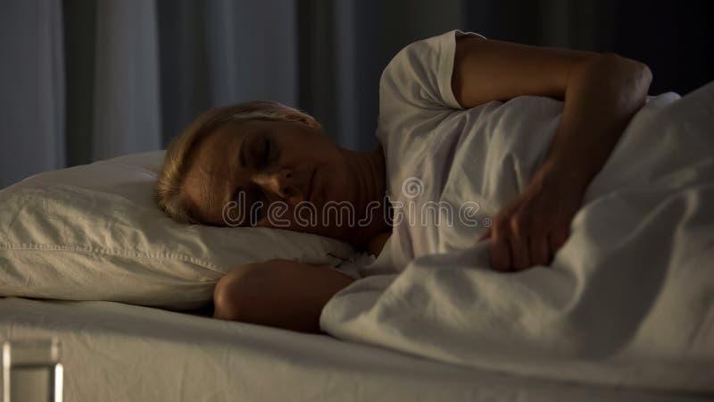 Vrouwelijke geduldige slaap in het ziekenhuisbed, gezondheidsprobleem, teruggetrokken leeftijdsonbekwaamheid stock fotografie