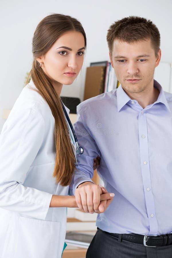 Vrouwelijke geneeskunde arts die haar patiënt helpen om na operati te lopen royalty-vrije stock foto's