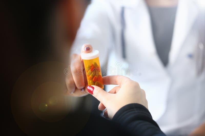 Vrouwelijke geneeskunde de greepkruik van de artsenhand van pillen en stock foto