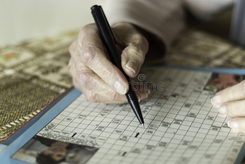 Vrouwelijke gepensioneerde die kruiswoordraadsels doen stock fotografie