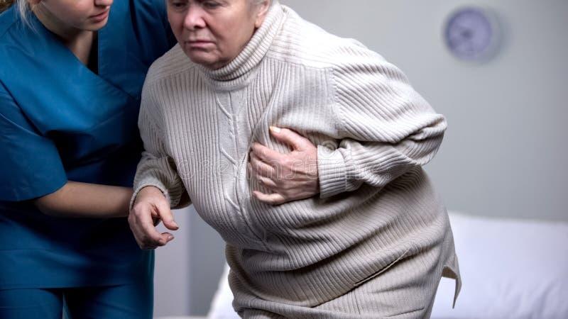 Vrouwelijke gepensioneerde die plotselinge hartpijn, verpleegster voelen die oude pati?nt, gezondheid helpen stock foto