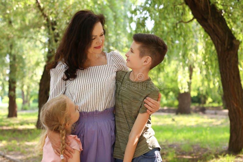 Vrouwelijke gepensioneerde met kleinkinderen in park royalty-vrije stock fotografie