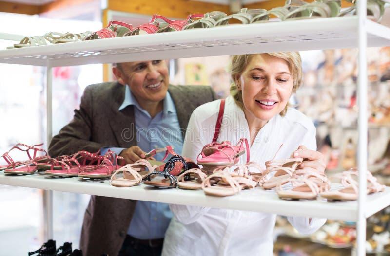 Vrouwelijke gepensioneerdenklant die paar sandals in schoenopslag kiezen stock foto's