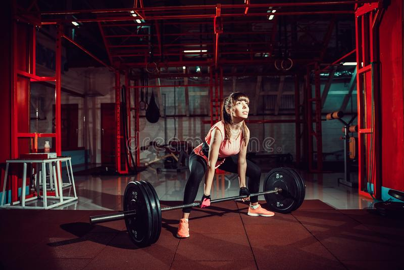 Vrouwelijke geschiktheid die doend deadlift oefening met gewichtsbar presteren stock afbeeldingen