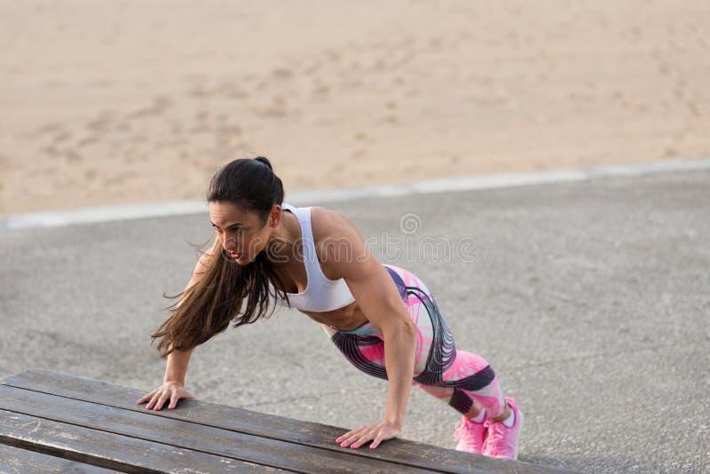 Vrouwelijke geschiktheidsatleet die duwups training buiten doen stock fotografie