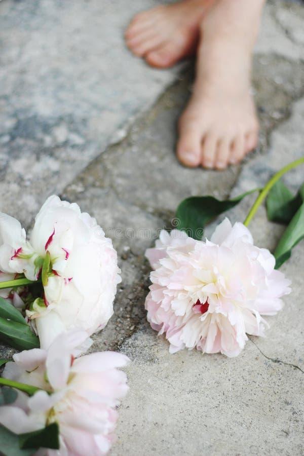 Vrouwelijke gestileerde voorraadfoto Verticale samenstelling Witte en roze pioenbloemen op grunge concrete vloer Defocusedjonge g royalty-vrije stock fotografie