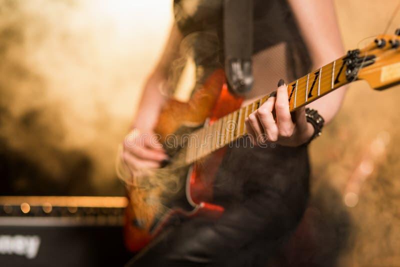 Vrouwelijke gitaarspeler in stadiumlichten stock foto's