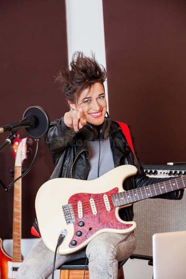 Vrouwelijke Gitarist Pointing While Performing in Studio stock foto