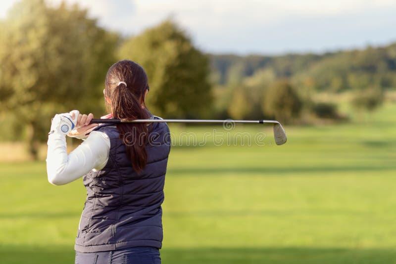 Vrouwelijke golfspeler die de golfbal slaan stock afbeeldingen