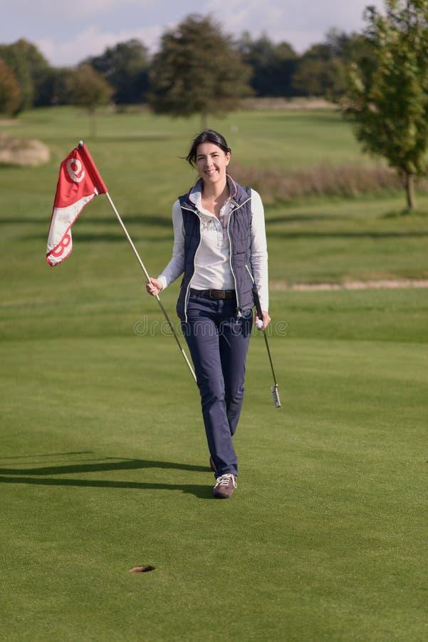 Vrouwelijke golfspeler die de vlag van het gat houden stock afbeelding
