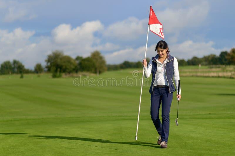 Vrouwelijke golfspeler die de vlag van het gat houden royalty-vrije stock fotografie