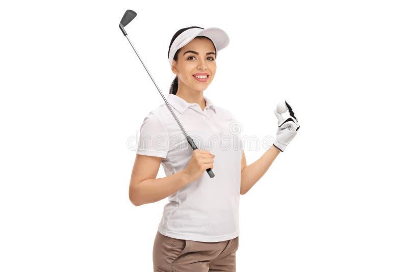Vrouwelijke golfspeler die een golfclub en een bal houden royalty-vrije stock afbeeldingen