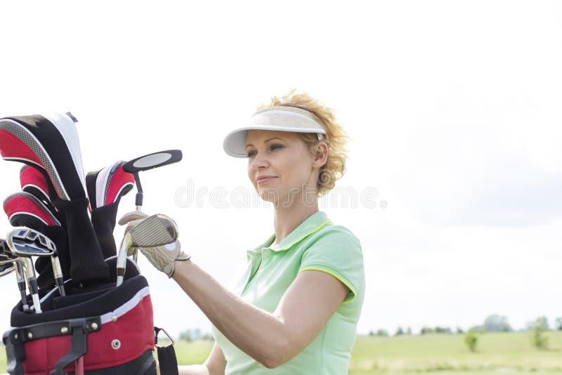 Vrouwelijke golfspeler met golfclubzak tegen duidelijke hemel royalty-vrije stock afbeeldingen