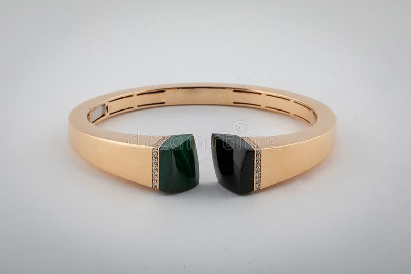 Vrouwelijke, gouden ring met diamanten, groene en zwarte steen in het midden, dat op een witte achtergrond wordt geïsoleerd royalty-vrije stock foto