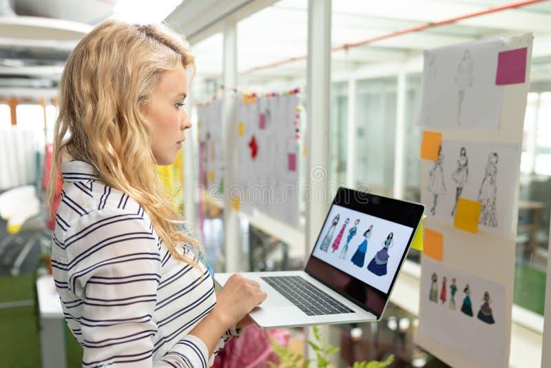 Vrouwelijke grafische ontwerper die laptop in ontwerpstudio met behulp van royalty-vrije stock fotografie