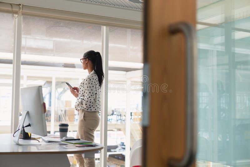 Vrouwelijke grafische ontwerper die mobiele telefoon met behulp van bij bureau in bureau stock afbeelding