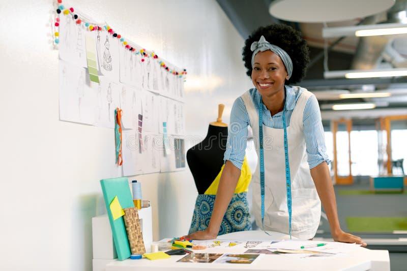 Vrouwelijke grafische ontwerper die op lijst leunen royalty-vrije stock foto's