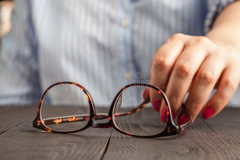 Vrouwelijke hand die bruine ontworpen glazen houden royalty-vrije stock foto's