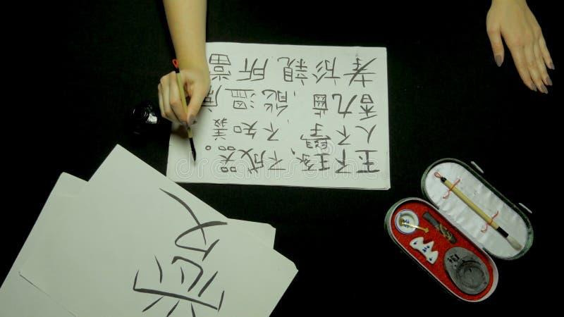 Vrouwelijke hand die Chinese kalligrafie schrijven die borstel en inkt op rijstpapier gebruiken Sluit omhoog bij de borstel van d stock foto