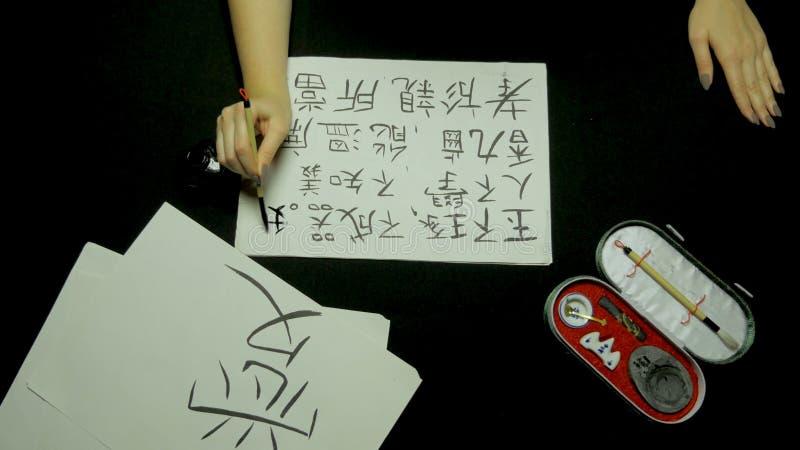 Vrouwelijke hand die Chinese kalligrafie schrijven die borstel en inkt op rijstpapier gebruiken Sluit omhoog bij de borstel van d stock foto's