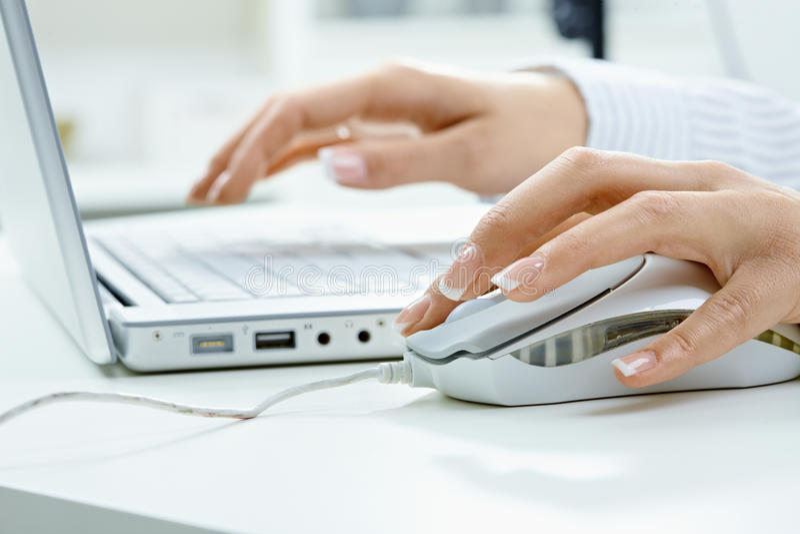 Vrouwelijke hand die computermuis met behulp van stock afbeeldingen