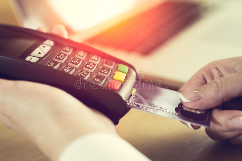 Vrouwelijke hand die creditcard opnemen in een lezer royalty-vrije stock foto's