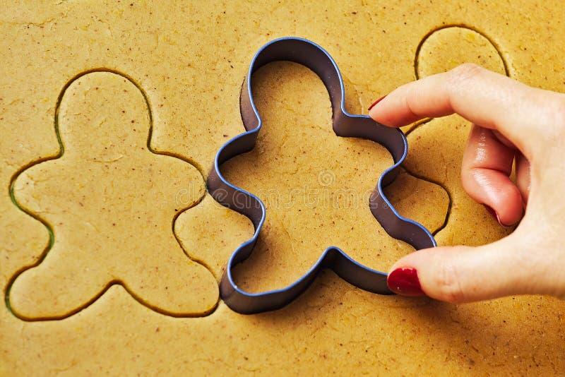 Vrouwelijke hand die de mensenkoekjes maken van de Kerstmispeperkoek stock afbeelding