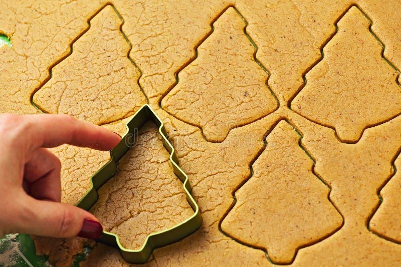 Vrouwelijke hand die de peperkoekkoekjes maken van de Kerstmisboom royalty-vrije stock afbeeldingen