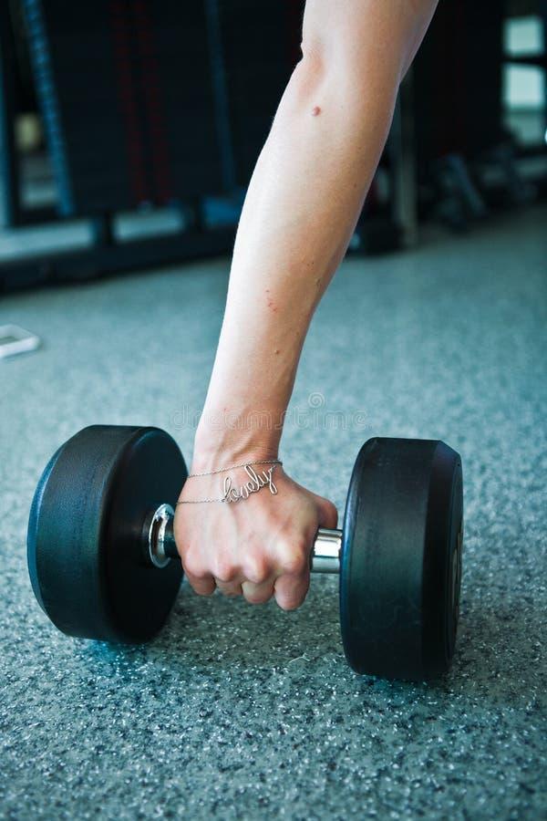 Vrouwelijke hand die dumbells uit rij van barbells in gymnastiek nemen royalty-vrije stock foto's