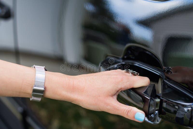 Vrouwelijke hand die een autodeur opent royalty-vrije stock afbeeldingen