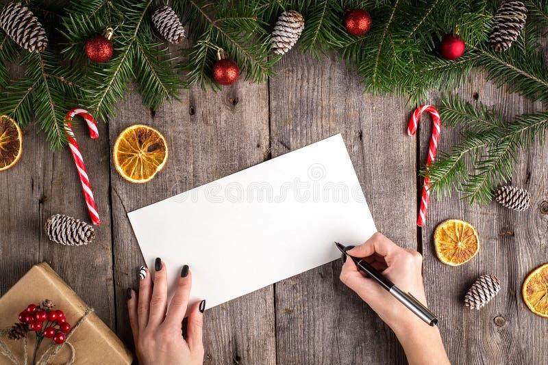 Vrouwelijke hand die een brief schrijven aan Kerstman op houten lijst stock fotografie