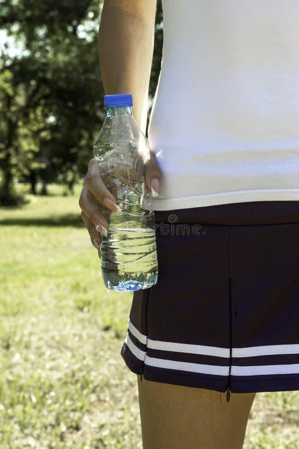 Vrouwelijke hand die een fles water houden stock afbeeldingen