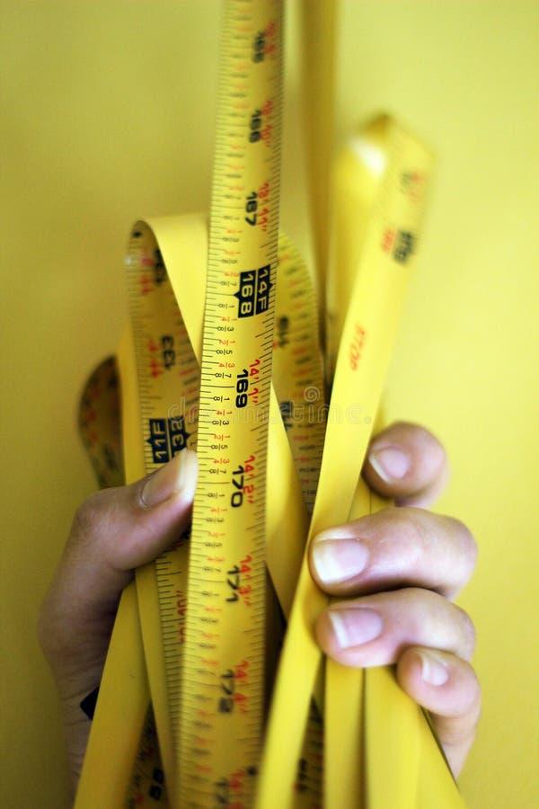 Vrouwelijke hand die een gele metermeasurer op een gele achtergrond houden royalty-vrije stock afbeelding