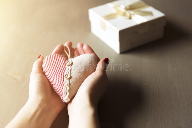Vrouwelijke hand die een giftdoos houdt Een gift van een hart, liefdadigheid, cas stock foto