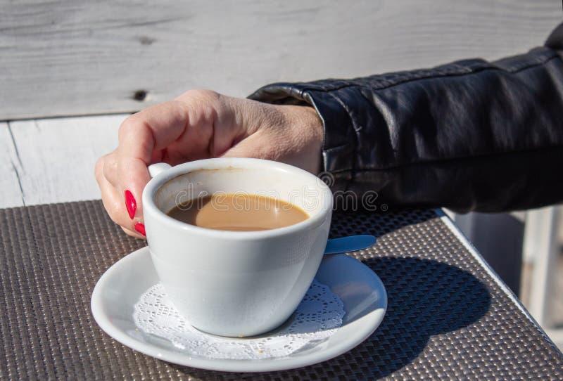 Vrouwelijke hand die een kop van koffie in een openluchtkoffie houden royalty-vrije stock foto