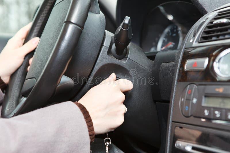 Vrouwelijke hand die een motor van een auto begint stock foto's