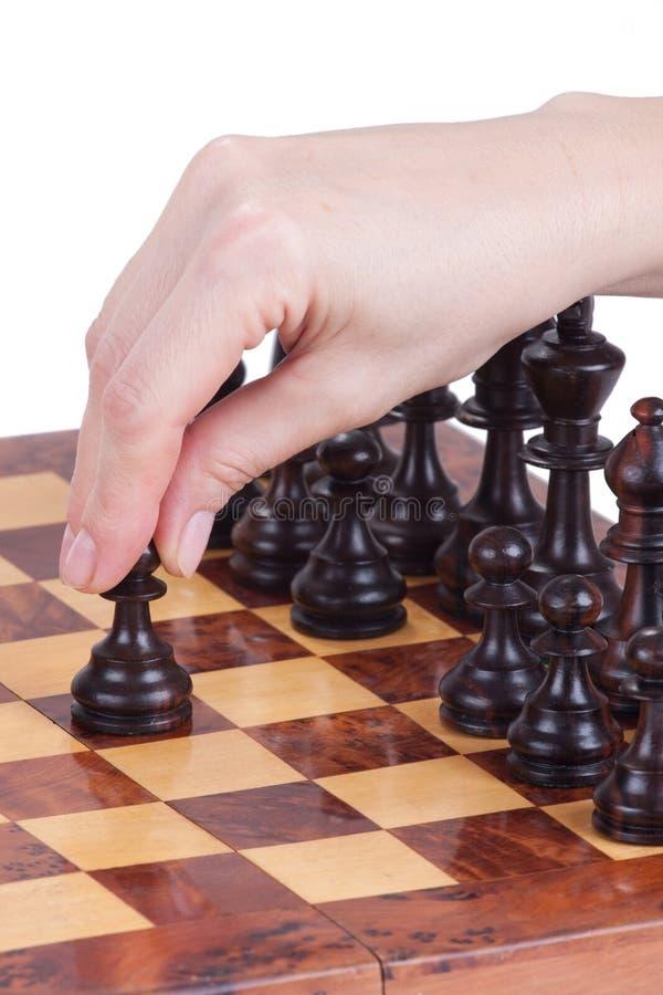Vrouwelijke hand die een pand op het schaakbord houden royalty-vrije stock afbeelding
