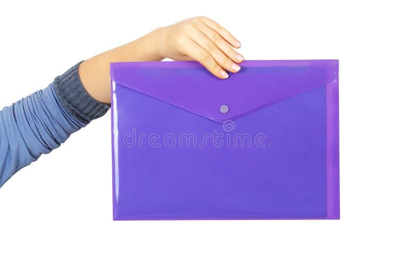Vrouwelijke hand die een purpere plastic omslag houden stock foto