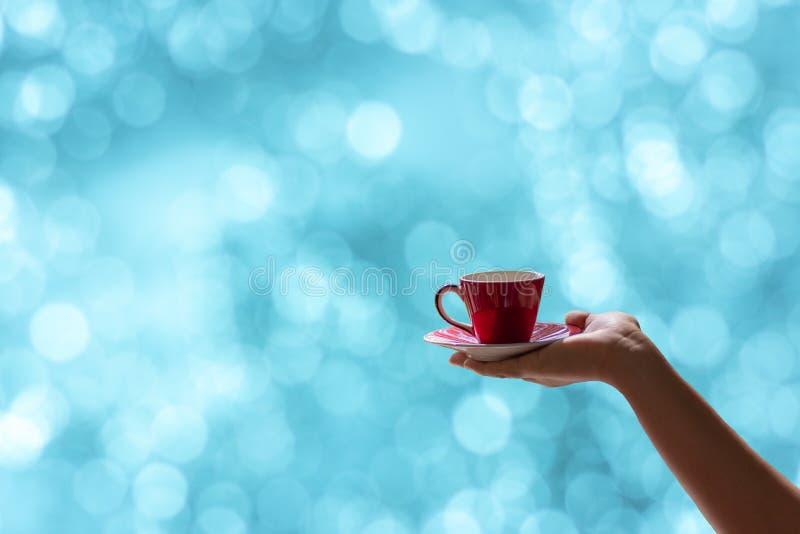 Vrouwelijke hand die een rode kop van koffie met vage blauwe bokehachtergrond houden royalty-vrije stock foto