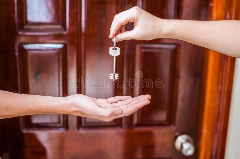 Vrouwelijke hand die een sleutel geven aan het huis een mensen` s hand op een achtergrond van een houten deur Het bezitten van on royalty-vrije stock afbeeldingen