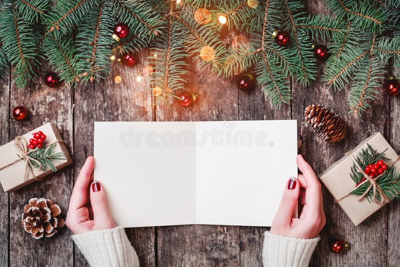 Vrouwelijke hand die en een brief schrijven lezen aan Kerstman op houten achtergrond met Kerstmisgiften, Spartakken en suikergoed stock foto's
