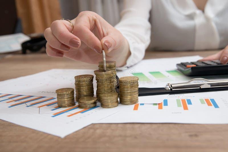 Vrouwelijke hand die euro muntstukken stapelen in kolommen boven bedrijfsdiagram royalty-vrije stock afbeeldingen